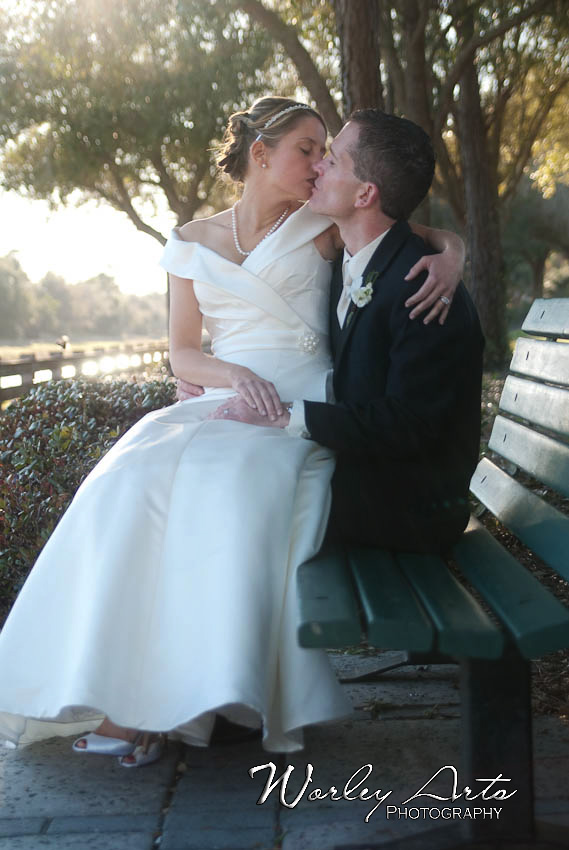 bride and groom kissing on park bench